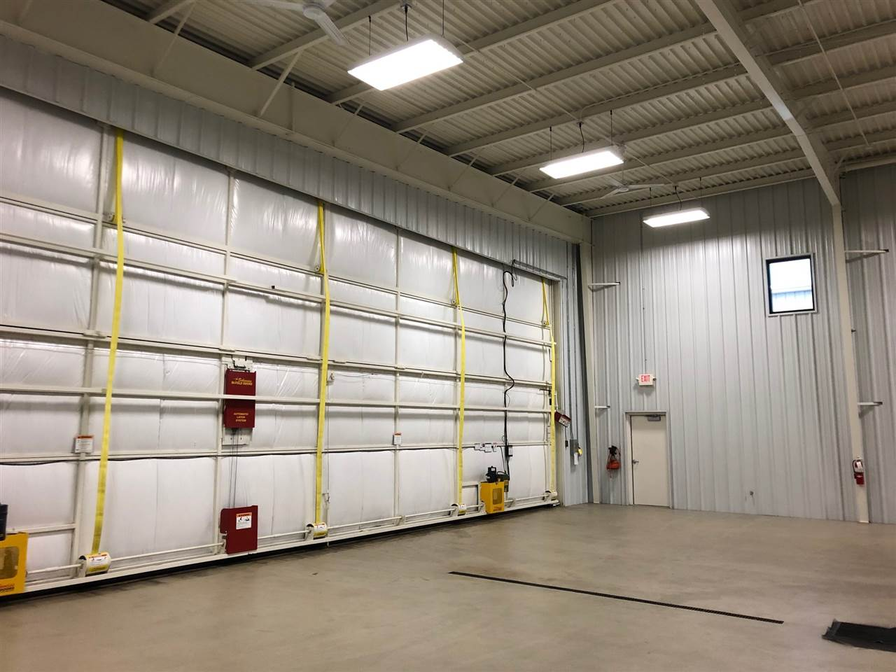 Remote controlled hangar bi-fold door measures 50 ft wide and 16 ft. vertical access. Epoxy coated floor for wash-down and snow melting. Apron has heating for snow melt.