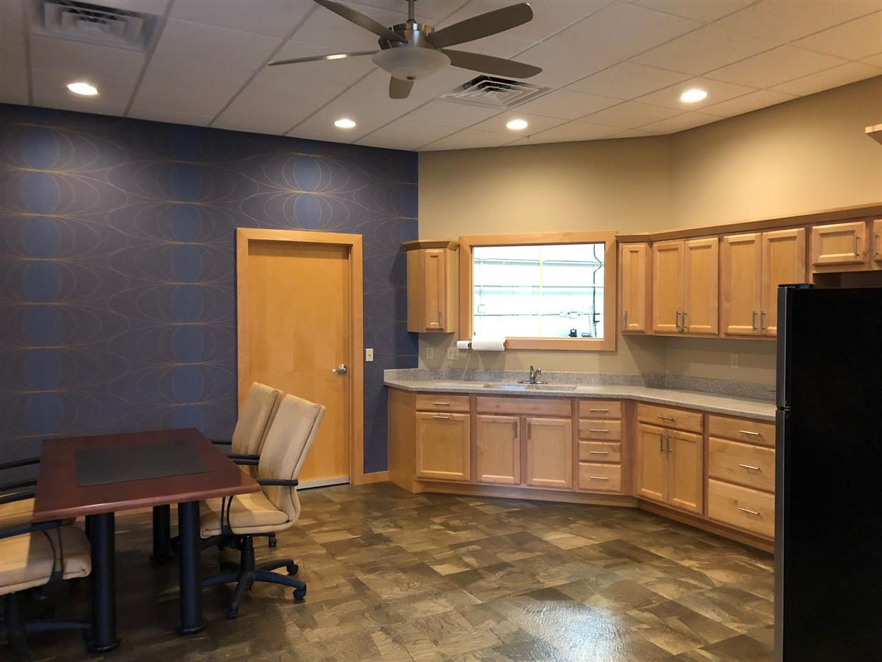 Hangar office kitchen with refrigerator, full cabinets, and coffee maker.